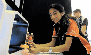 Wheely good result: Solar Eclipse team member Laura Bocks, 14, with their F1 model car, which cleared the 20 metre racetrack in 1.147 seconds propelled by a soda bulb. Picture: Gene Ramirez